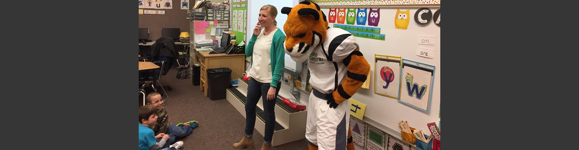 Idaho State University tiger mascot with teacher in front of students.