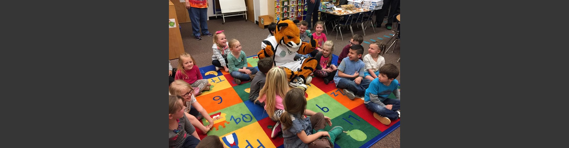 Idaho State University tiger mascot sitting on the floor with the kids.