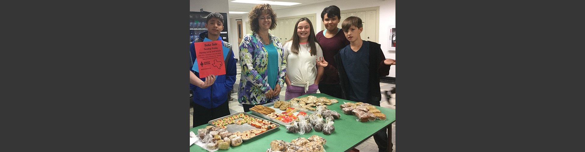 Students and teacher posing with bake sale items for fundraiser.