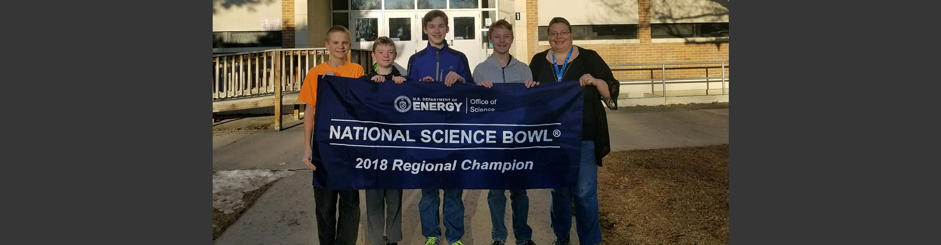Alameda Middle School students and teacher in front of school with National Science Bowl 2018 Regional Champion flag.